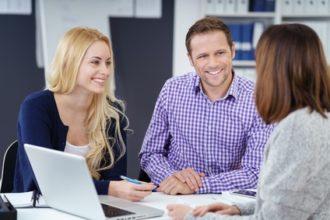 Lächelndes junges paar in einem gespärch mit einer kundenberaterin